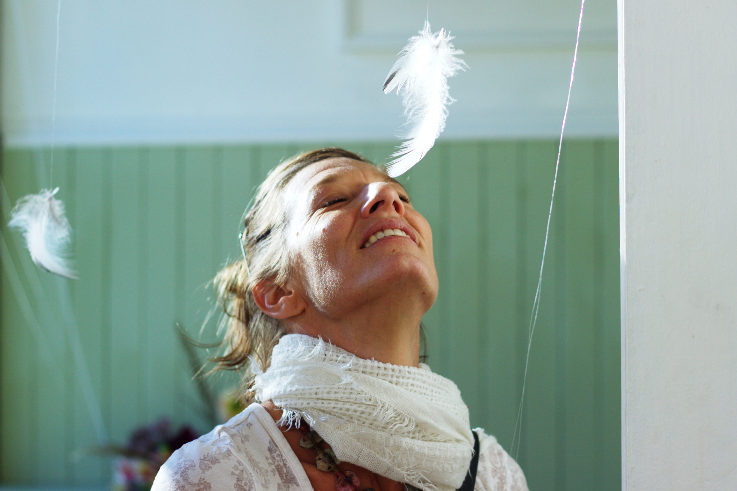 Woman looking up with white feather on her nose